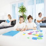 Happy family are resting at home, children playing with puzzle.